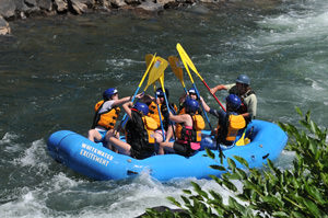 group in raft with paddles in the air on middle fork american river rafting california