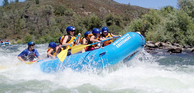 river raft crashing through rapid